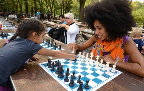 A woman and a girl challenge each other to a chess game