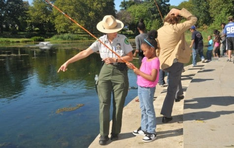 a park ranger teaches a girl how to fish at a lake