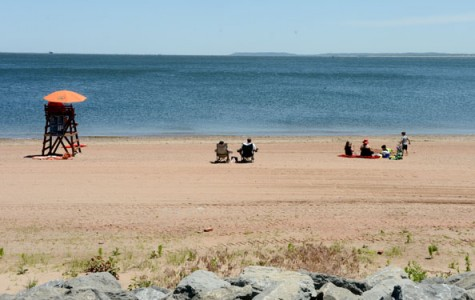 Beachgoers lounge in their beach chairs at a beach where a lifeguard is on duty
