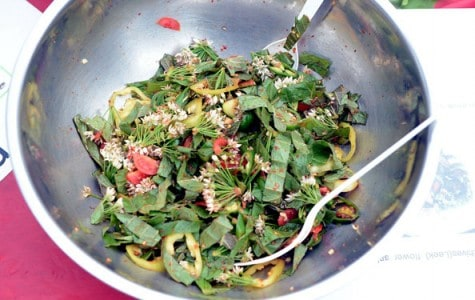 a bowl of salad made of vegetables and flowers