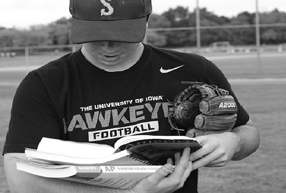 STOPPING STEREOTYPES. Picking up books on the field, Justin Stark '16 breaks the social stereotype of athletes. Stark balances his sports and academics on and off the field.