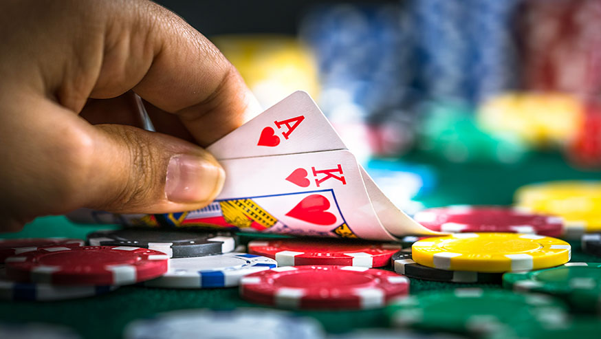 Hand tipping up Ace and King of Hearts with poker chips underneath