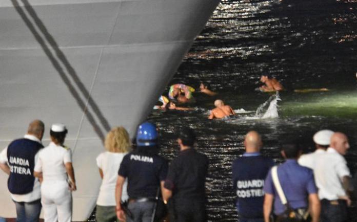 Si susseguono al porto di Catania le manifestazioni a favore dello sbarco dei migranti bloccati sulla nave Diciotti. Nell'immagine alcuni dei giovani che si sono tuffati in acqua e sono riusciti ad arrivare a nuoto sotto bordo. Catania, 25 agosto 2018 ANSA/ORIETTA SCARDINO