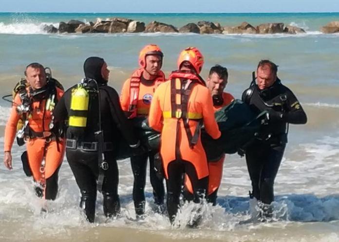 Sommozzatori portano a riva il corpo di uno dei due ragazzini dispersi in mare ad Ortona (Chieti) e poi trovati morti, 15 agosto 2019. I corpi sono stati rinvenuti su una scogliera frangiflutti, in due punti distinti, ma a pochi metri di distanza uno dall'altro. ANSA/LORENZO DOLCE