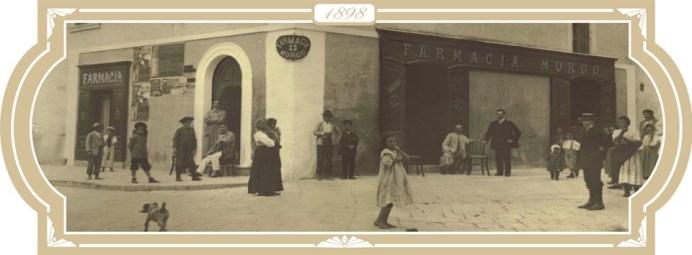 1898-La farmacia centrale Murgo fondata dal farmacista-chimico dott. Lorenzo Murgo-a destra nella foto, seduto all'ingresso della sua farmacia