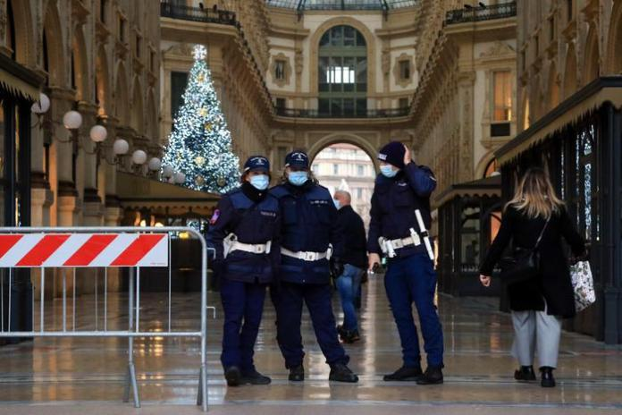 Local police officers check the entrances to the Galleria Vittorio Emanuele for any gatherings due to shopping, amid the second wave of the Covid-19 Coronavirus pandemic, in Milan, Italy, 05 December 2020. Italian government on 03 December passed a strict package of restrictions aimed at stopping the festive season fuelling a third wave of COVID-19 contagion. The package includes a ban on travelling between regions between 21 December and 6 January and a ban on moving outside one's home town on Christmas Day, St Stephen's Day and New Year's Day. The government has also maintained the current night curfew, with people not allowed out of their homes from 10pm until 5am, except for work or health reasons or other urgent situations. ANSA/ PAOLO SALMOIRAGO