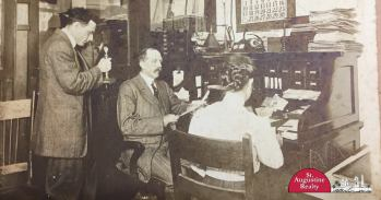 Old photo of three people sitting at a desk