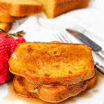 Image of Keto French Toast with syrup and strawberries with burred loaf and slices in the background.
