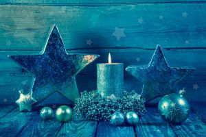 First advent: one burning golden candle on a wooden blue background.