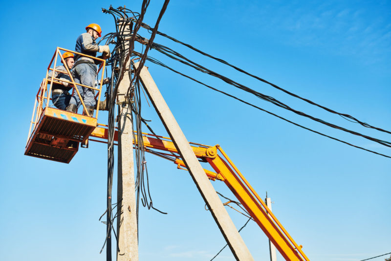 Electrician lineman repairman worker at climbing work on electric post power pole. Electrification.