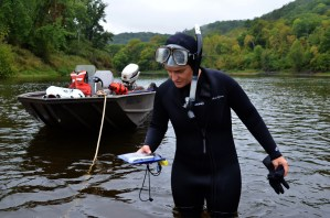 Fish and wildlife biologist Tamara Smith looks at her GPS as she locates an underwater line in the St. Croix River.