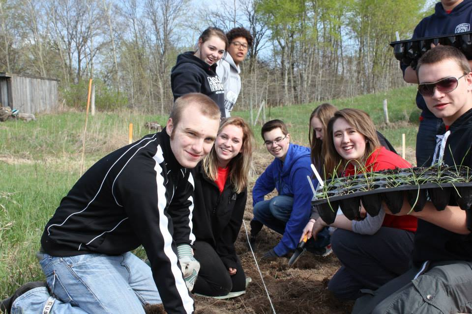 Students plant Dotted-Blazing Star seeds saved from the site of the new Stillwater Bridge. The endangered plant's species is 8,000 years old.