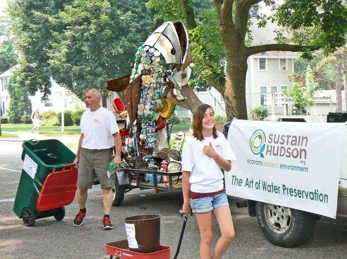 Several volunteers from the RiverFest committee and Hudson Grocery Co-op (HGC) joined the Scrappy float during the Boosters' Days parade. In an effort to help keep the river clean, RiverFest provided trash cans for parade goers at the end of the parade. Volunteer Lily Jorgenson gives a thumbs-up for Hudson RiverFest, while HGC volunteer Randy Smith pulls one of the trash cans.