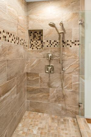 Large Shower with removable shower head and beautiful tile work.