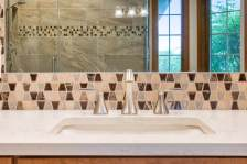 White quarts counter top with brushed nickel faucet and beautiful mosaic tile backsplash.