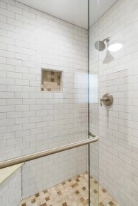 Old shower surround is removed and replaced with a white subway tile shower in the master bathroom.