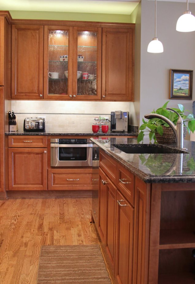 Open concept kitchen includes maple recessed panel cabinets in chestnut