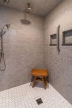 Large walk in shower boasts multiple shower heads for an at home spa experience.
