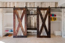 Rustic barn doors open for hidden storage for all of this family's lake and and beach necessities.