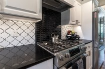 Black and white tile work pairs perfectly with black quartz counter top