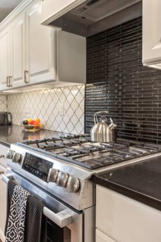 Black tile accent adds a design element above range.