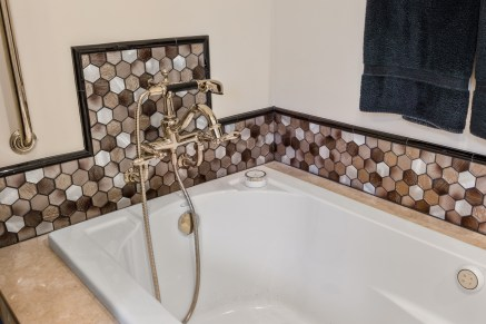 Large bathtub with elegant faucet and mosaic tile work in neutral tones.
