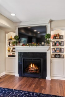 Living room remodel includes custom fireplace surround, mantle and bookcases