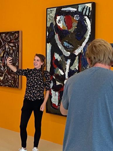 Verslaggever Lonneke neemt een selfie bij het werk van Karel Appel..