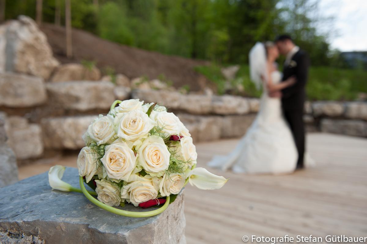 Brautstrauss mit Brautpaar im unscharfen Hintergrund