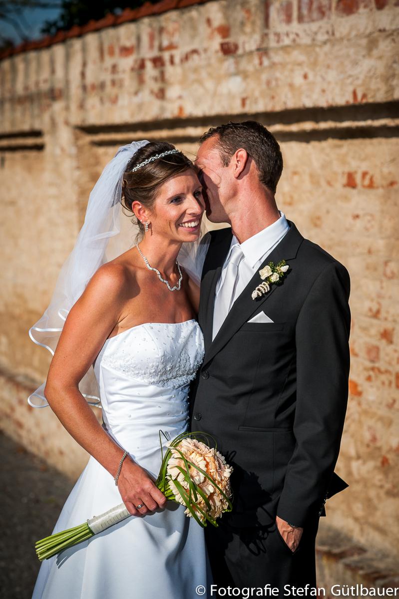 Brautpaar in den Grünanlagen des Klosters Fürstenfeld stehend vor einer Mauser