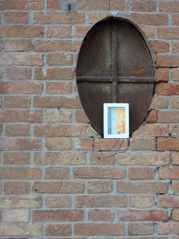 un dono d'arte abbandonato di fronte a una finestra ovale