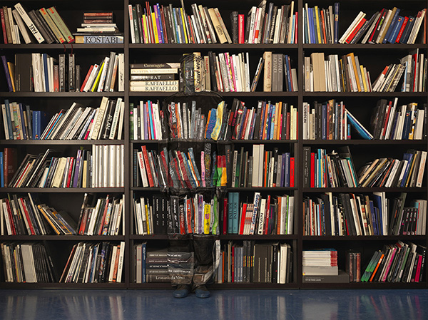 sagoma di un uomo nascosta tra i libri
