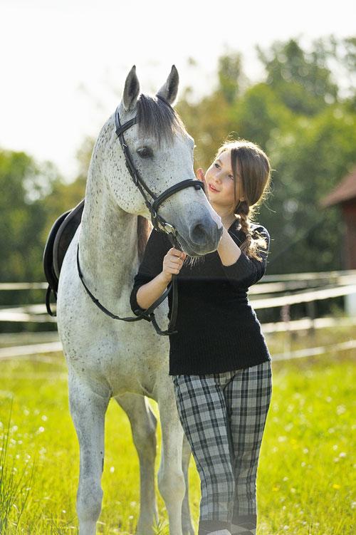 En vit häst blir en bra reflexskärm för porträtt utomhus i solljus