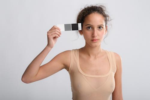 Tjej som fotomodell med gråkort i fotostudio