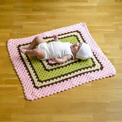 Bebis som modell på lekfilt vid fotografering till bok om virkade mormorsrutor. Fotograf Stefan Tell