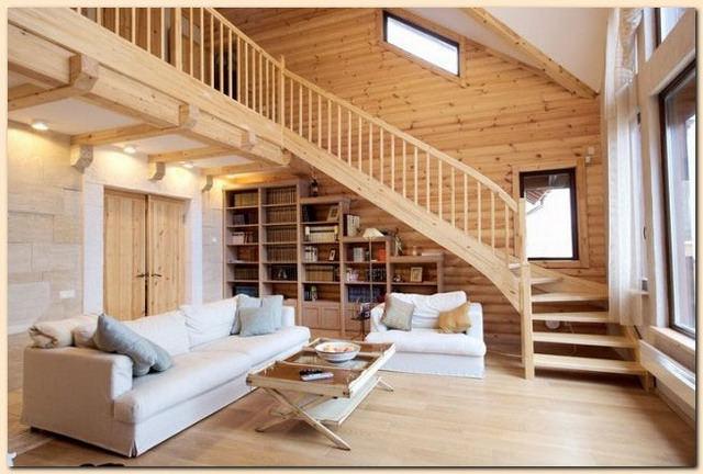Amenajare sub scara de lemn cu sofa si biblioteca