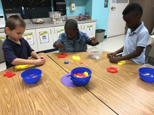Students sorting shapes by colors and shapes