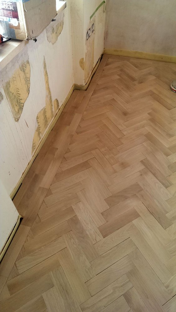 Oak herringbone parquet laid with 2 block border in