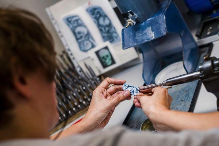 Anja Schüssler beim Gravieren an der Gravierspindel, im Hintergrund Zeichnung und Gravierwerkzeuge