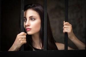 Belle jeune fille tenant des barreaux et regardant au loin dans Vieux-Montréal