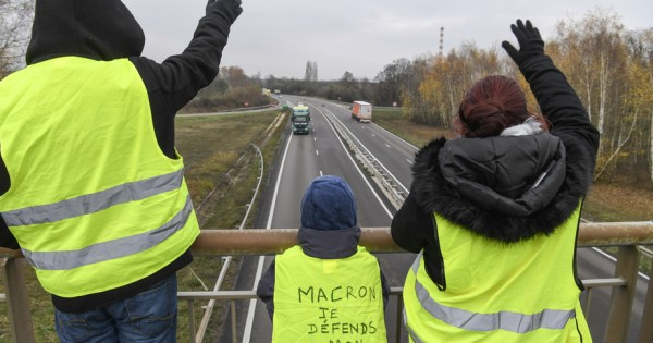 "Protesters wearing yellow vests (gilets jaunes in French) onto which one of them is written ""Macron I defend my future"" wave on a bridge over the N70 road, on the fifth day of a movement against high fuel prices which has mushroomed into a widespread protest against stagnant spending power under French President on November 21, 2018, near Montceau-les-Mines, central France. (Photo by PHILIPPE DESMAZES / AFP)"