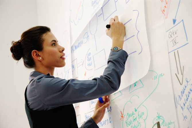 Hispanic businesswoman drawing on paper in office