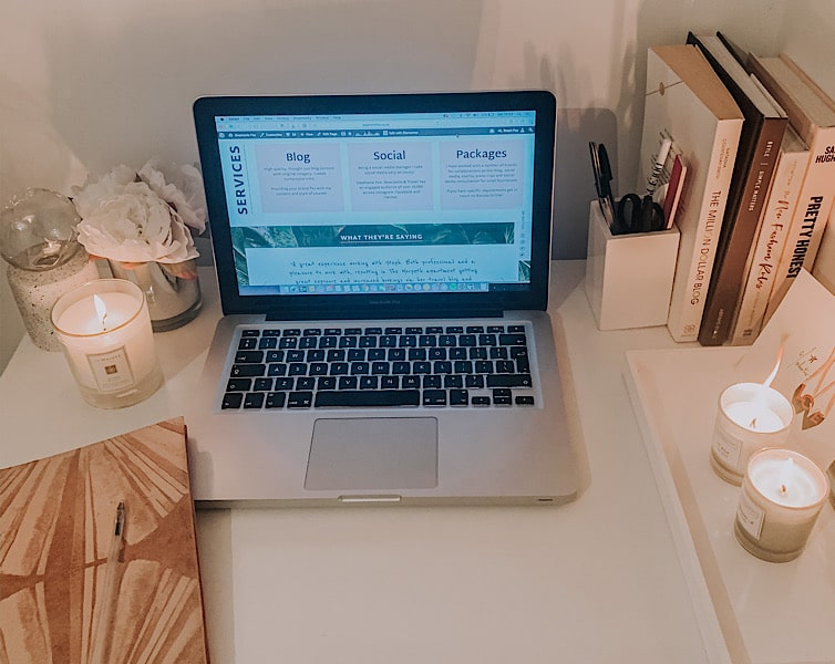 laptop on a desk with candles