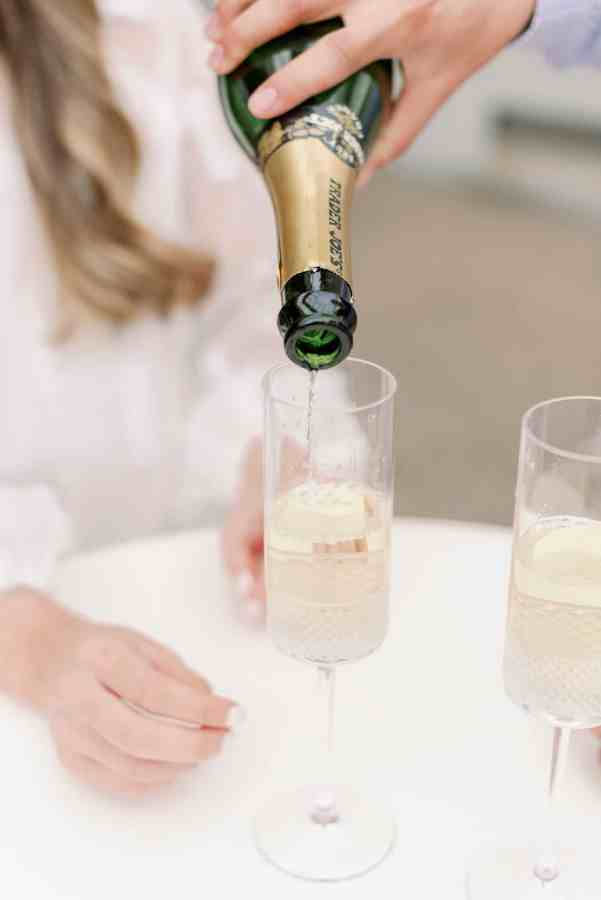 Couple pouring champagne at engagement session