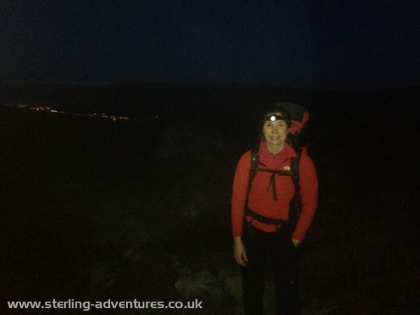 Laetitia on the approach up Allt a' Mhuilinn, the lights of Fort William are just visible behind.