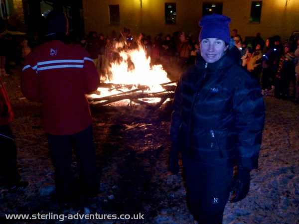 Laetitia warming herself at the celebration bonfire in Cogne town centre