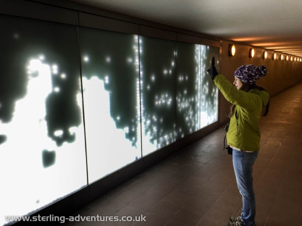 """Laetitia having fun with the subway art installation leading away from the Berlin Victory Column.  The wall """"watches"""" you and reflects your outline back with light..."""