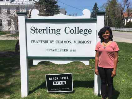 color photo of Neetu Raju standing in front of the Sterling College sign