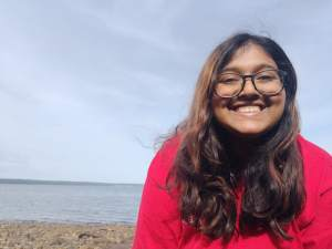 Person smiling standing on a beach