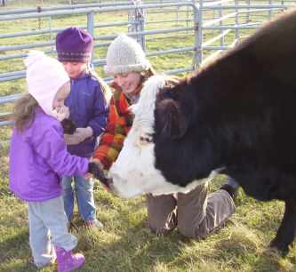 a woman and two children dressed for winter with a cow